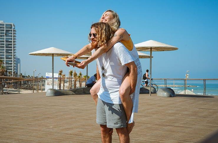 man piggybacks a woman at the beach