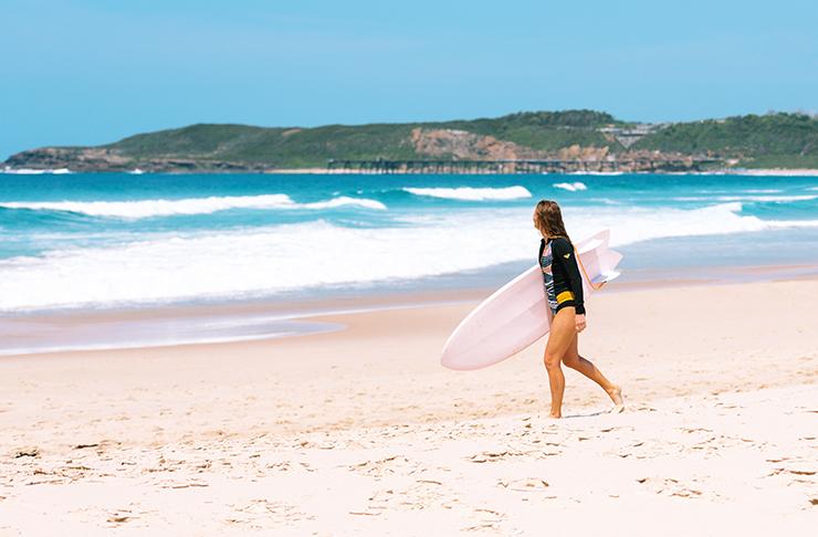girl with surfboard on beach