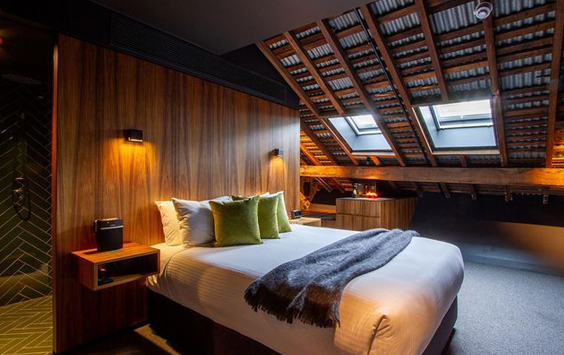 the interior of Moss Hotel, an arched roof and timber walls frame a bed.