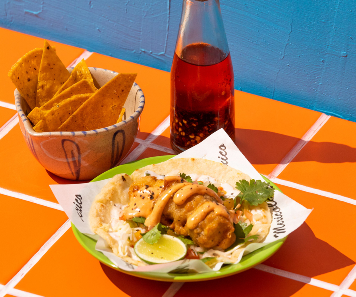 tacos and chips on tiled table with sangrita bottle
