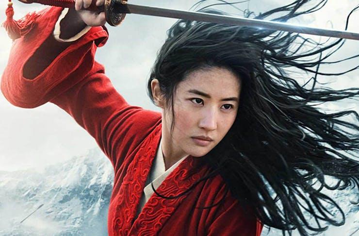 mulan, dressed in red, raises her sword in battle.