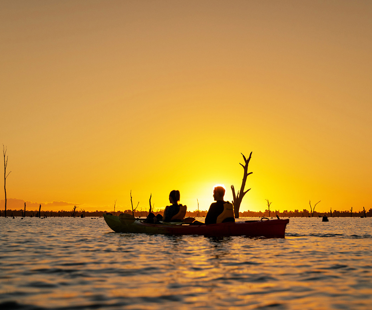 two people kayaking on river at sunset