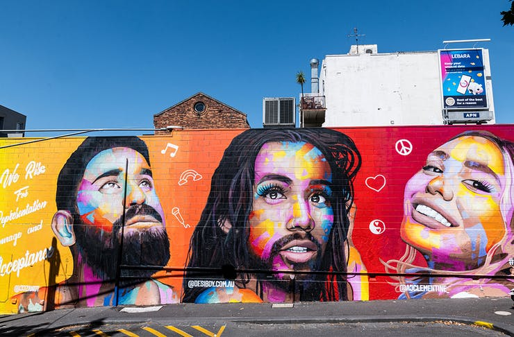 A colourful mural painted on a brick wall in Melbourne, a bright blue sky behind. The mural features the faces of AJ Clementine, Jeff van de Zandt and Roshan Nausad.