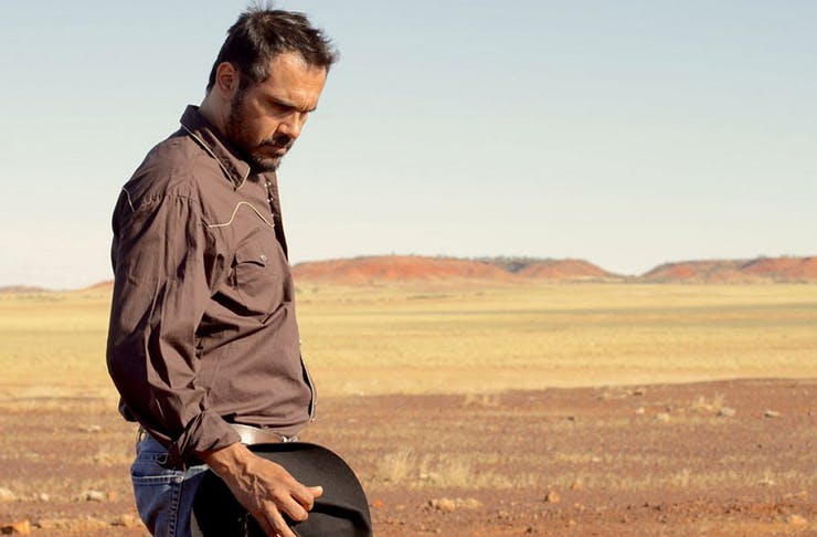 A man holds a hat in his hands as he looks at the ground. A stunning desert behind him.