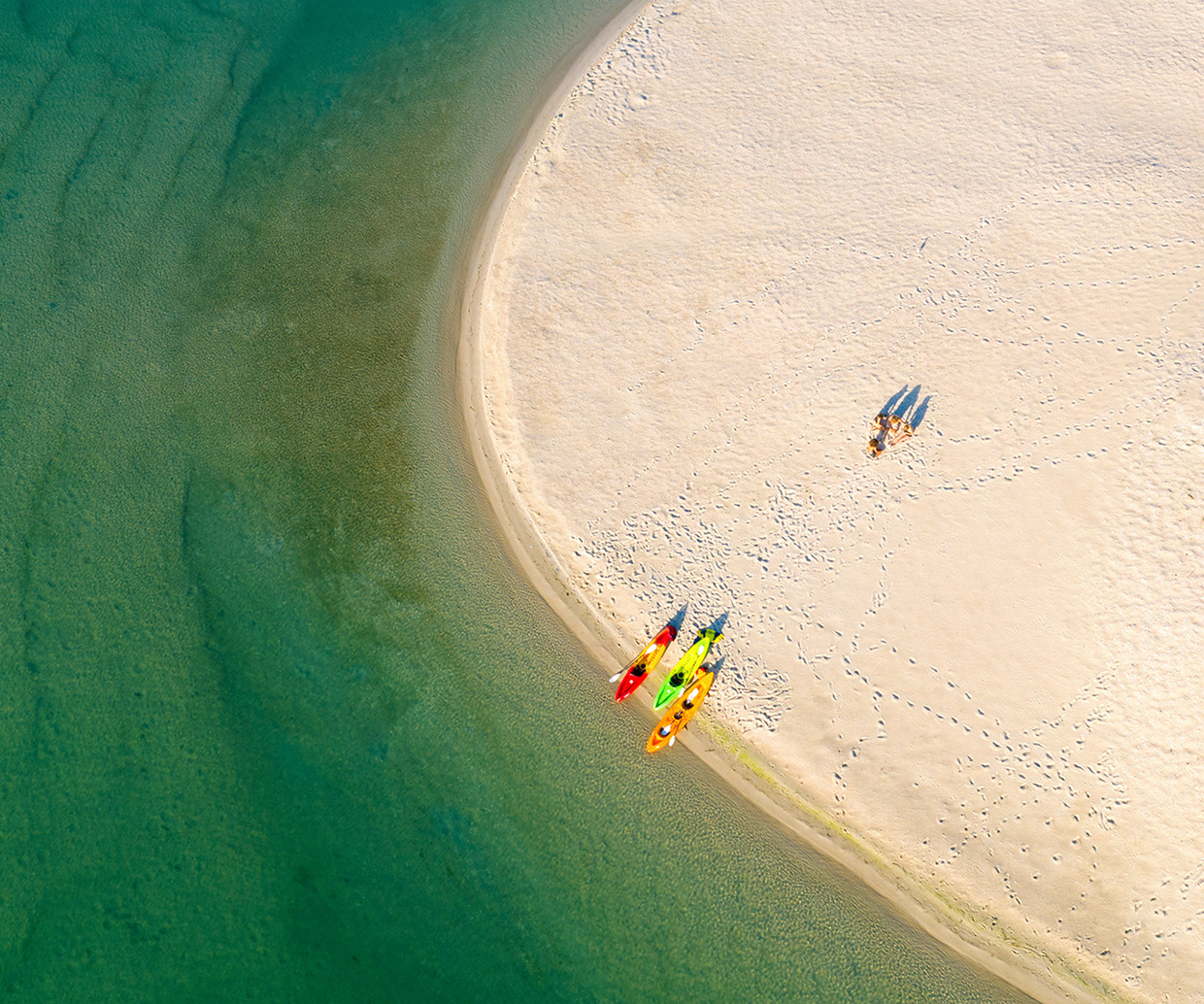 aerial view of two people with kayaks on sand bank
