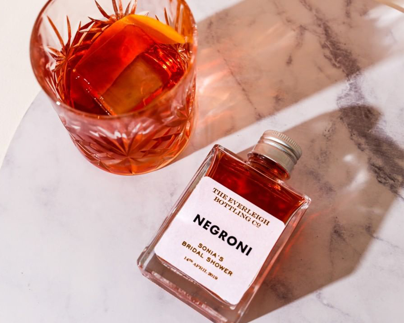 A glass and small bottle of negroni lay on a marble table.