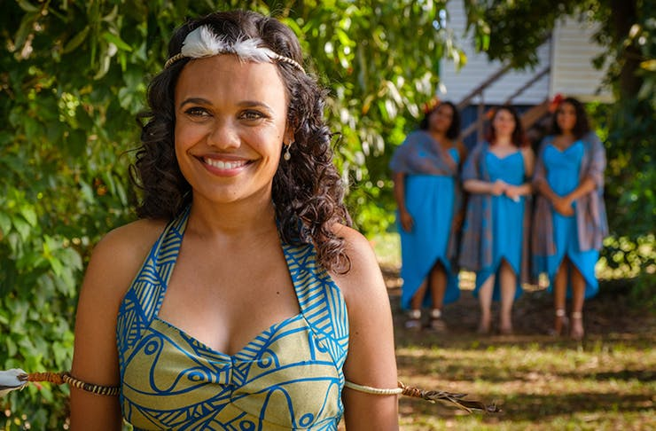 Image from Top End Wedding on Netflix. She smiles, while wearing a colourful dress. Behind her stands three women in blue dresses.