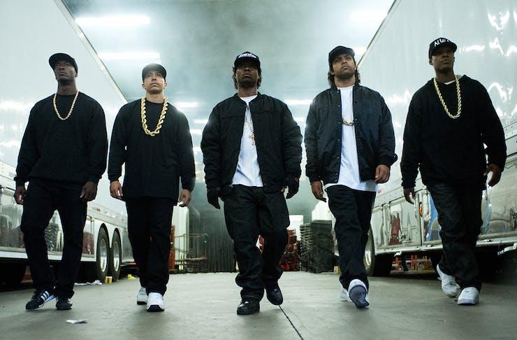 the members of N.W.A, dressed in black, walk down a hallway.