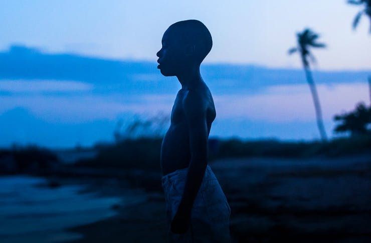 the silhouette of a young African American boy stands on a beach at dusk. Palm trees blow in the wind behind him.
