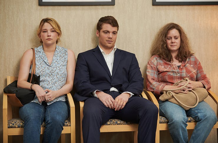 two women and one man sit in chairs in a waiting room.
