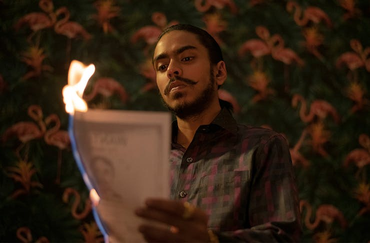 a young man holds a piece of paper on fire.