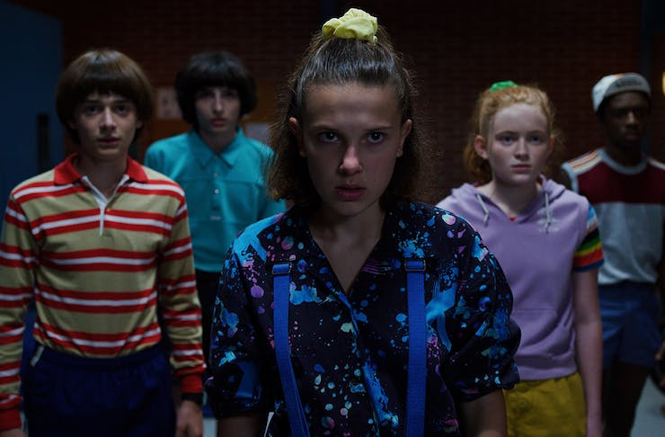 a group of teens gather in a group at night.