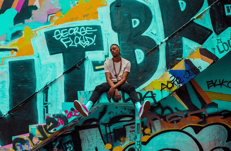 a man sits on the steps in front of a graffiti wall