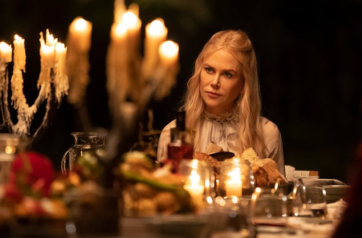 Nicole Kidman in Nine Perfect Strangers sits at a dinner table laden with candles and food.