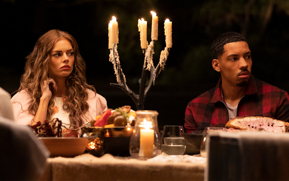 a young man and woman sit at a dinner table laden with candles and food.