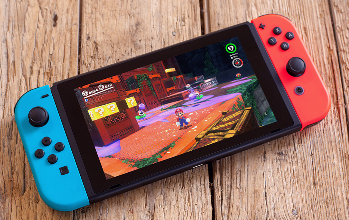 a blue and red Nintendo Switch on a timber table.
