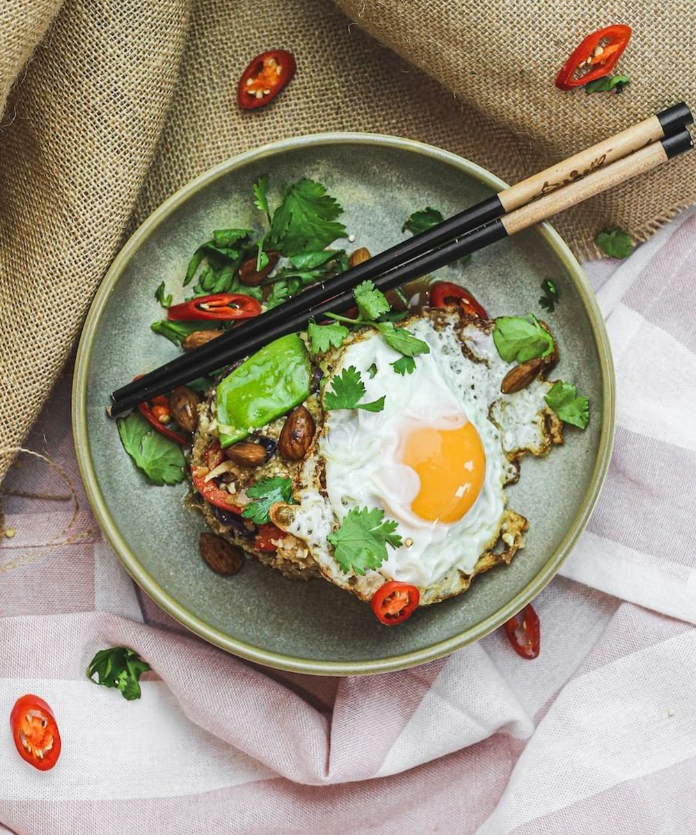 a bowl with rice and a fried egg, chopsticks lay on top