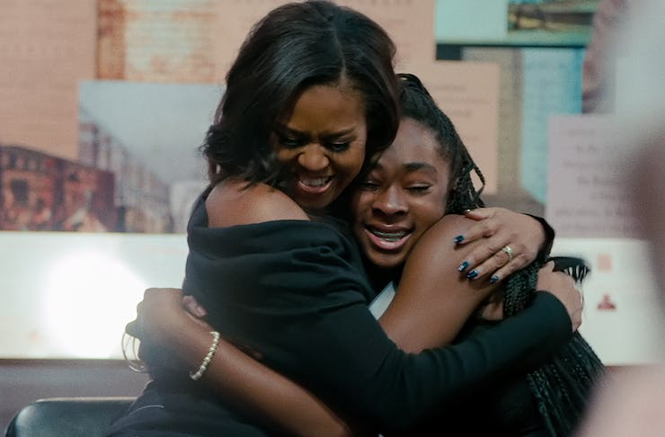 Michelle Obama, dressed in black, holds back tears as she hugs an emotional teenage girl.