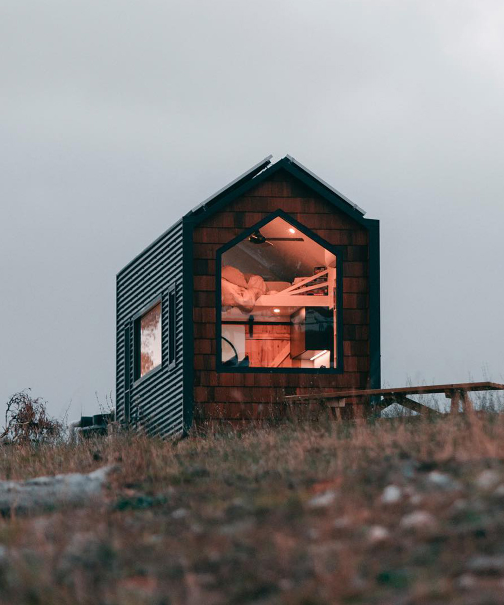 The exterior of a tiny home and night. The light shines from inside.