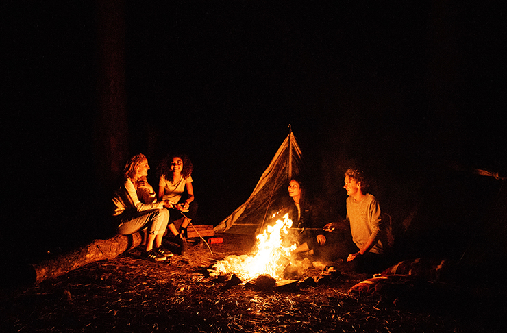 people sitting around a campfire in a forest at night