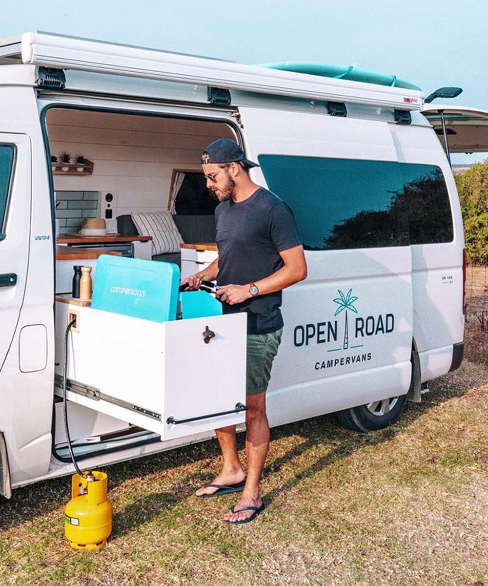 A man cooks next to the Open Road Campervan