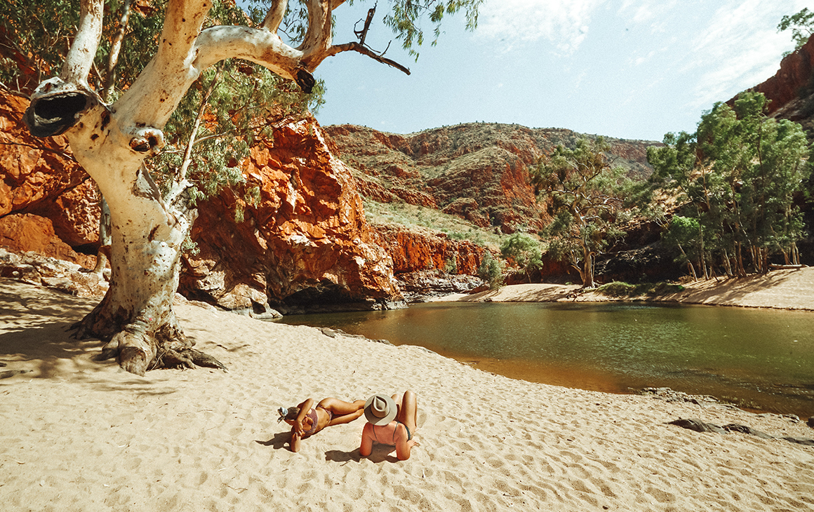 a young man and woman recline on the sand next to natural pool at Ormiston Gorge.