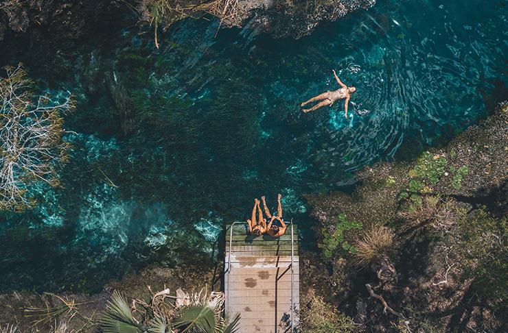 aerial of people floating in crystal clear creek