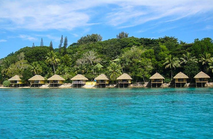 a line of wooden huts sit against a sparkling blue ocean