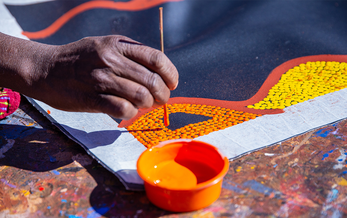 a close up of an artists hand as they work on a dot painting.