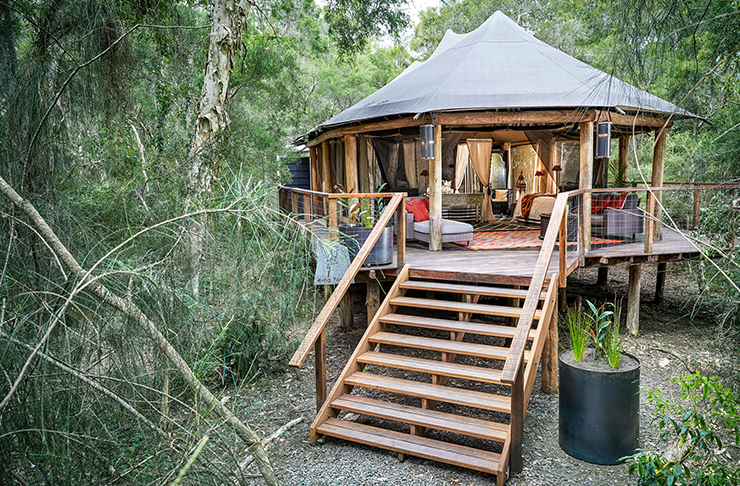 a gorgeous tent sits on a wooden deck in the middle of the bush.