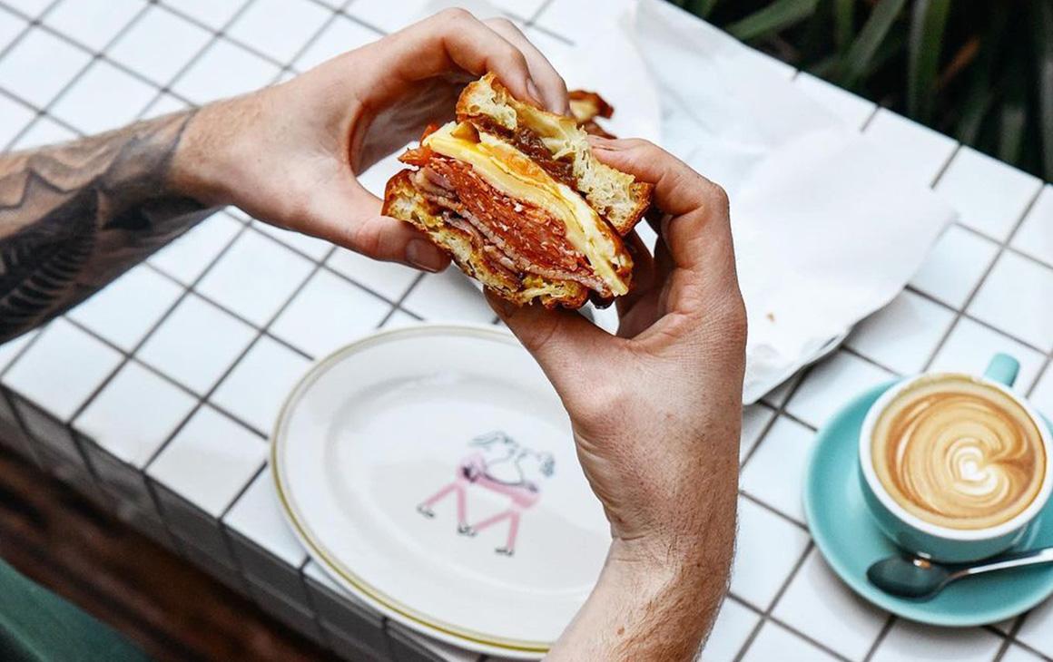 tattooed hands hold a breakfast sandwich