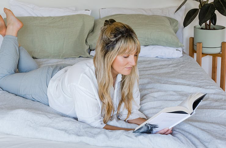 Girl reading a book on top of a bed with a plant in the background.