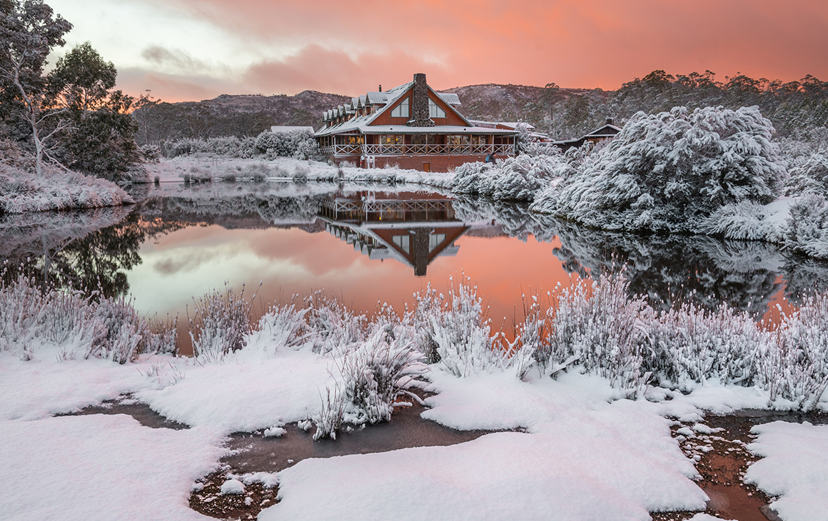 A dusty peach sky and a snow-capped Peppers Resort at Cradle Mountain