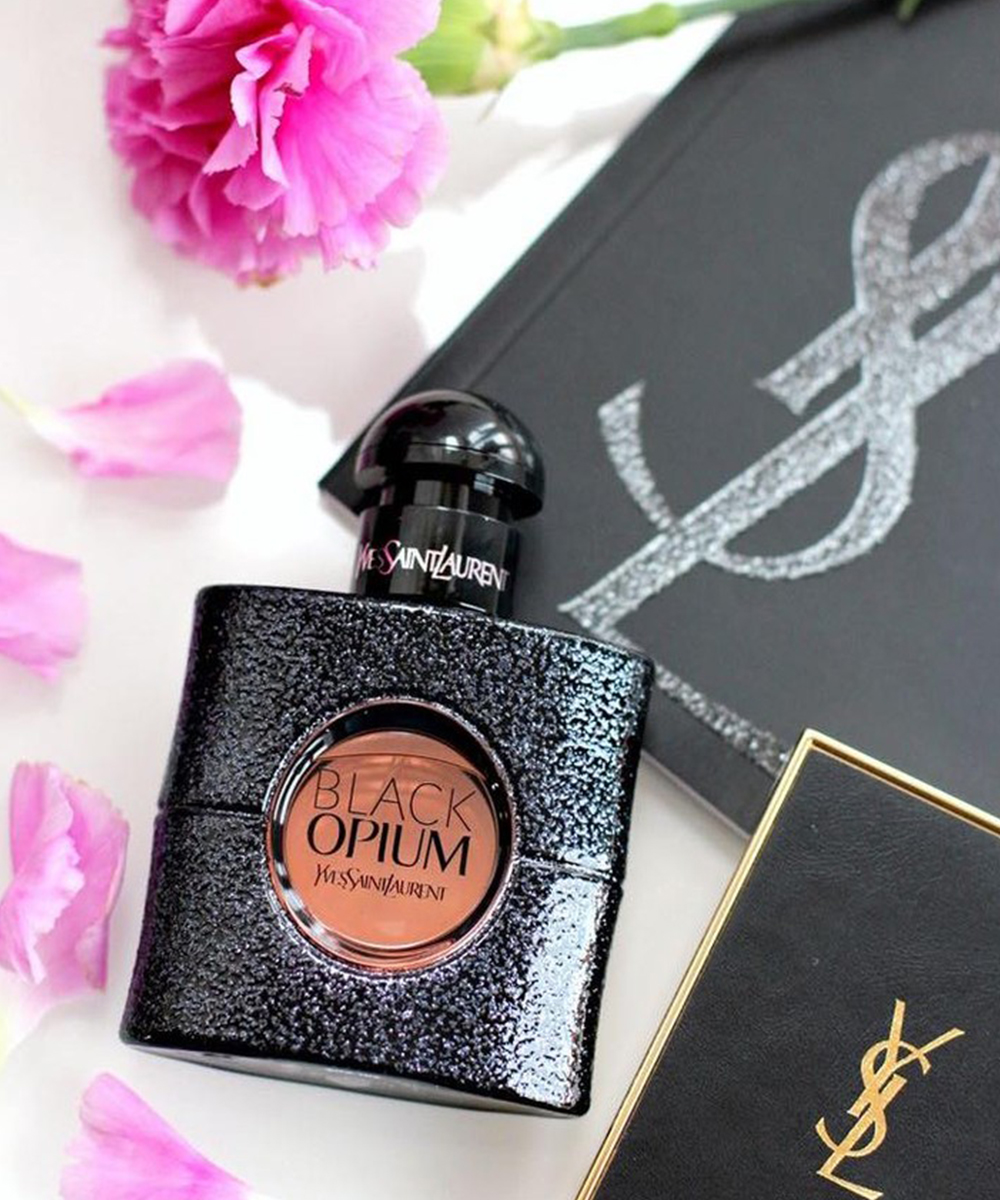 a small black bottle of perfume, with a pink flower next to it.