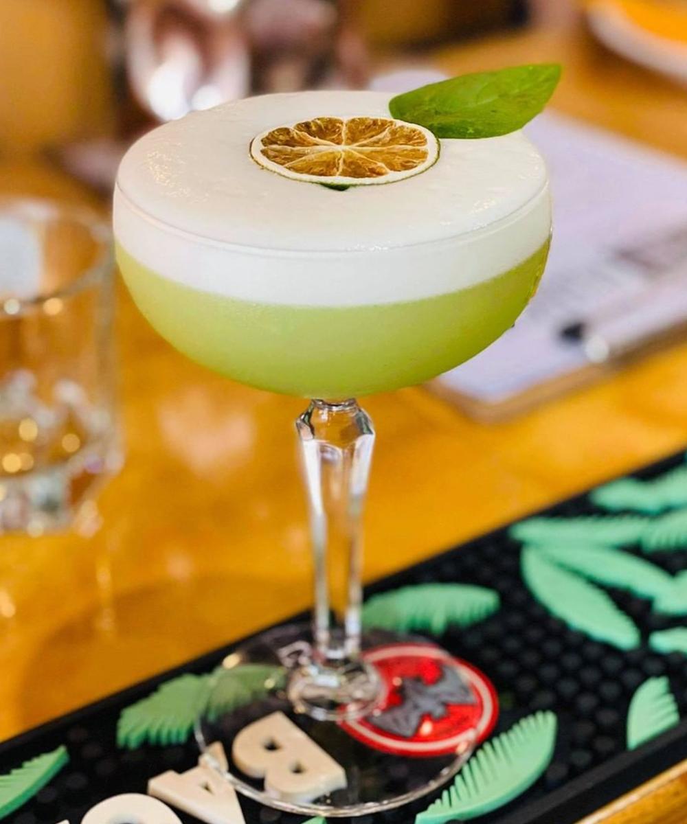 a lime coloured cocktail on a bar.