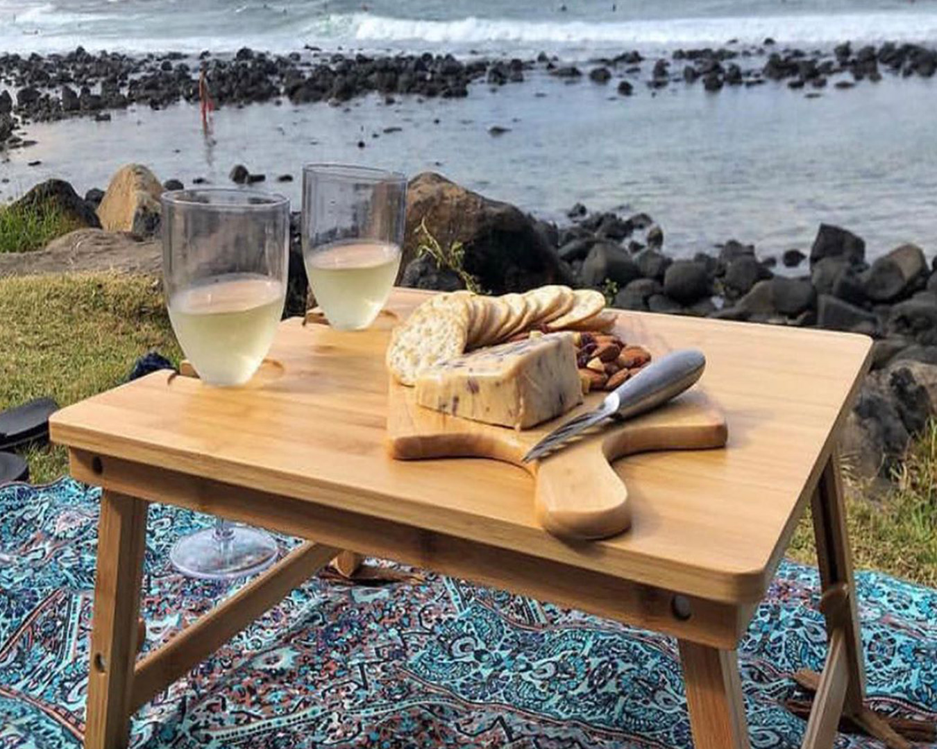 a small wooden picnic table with cheese, crackers and wine on it, sits next to the ocean.