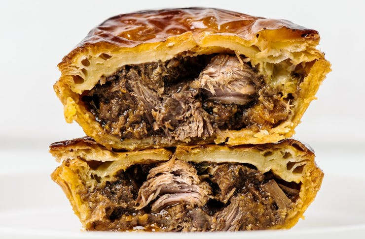 juicy meat pie cut in half and stacked
