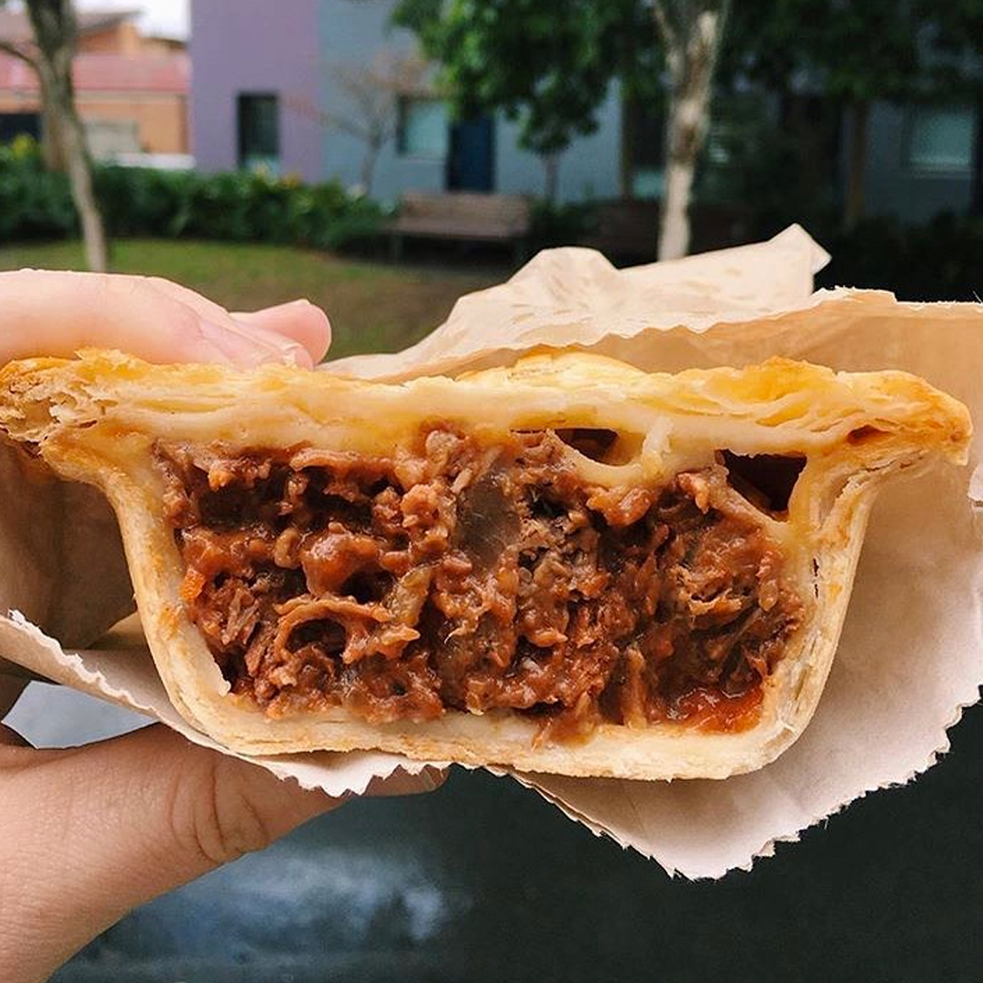 hand holding meat pie cut in half