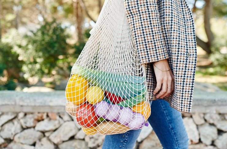 a woman has a reusable bag slung over her shoulder, filled with colourful fruit and veg.