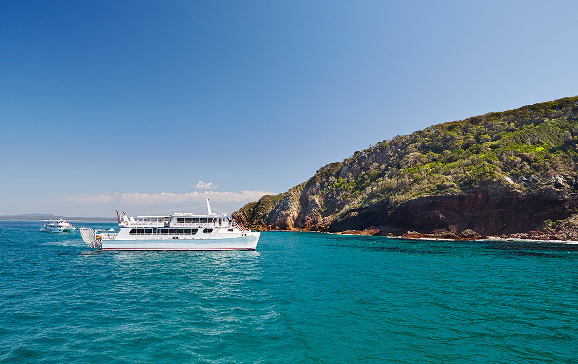 a boat pulls into the coastal town of Port Stephens