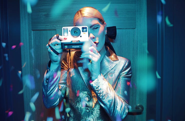 a woman, bathed in a blue light and surrounded by confetti, takes a photo on an old polaroid camera.