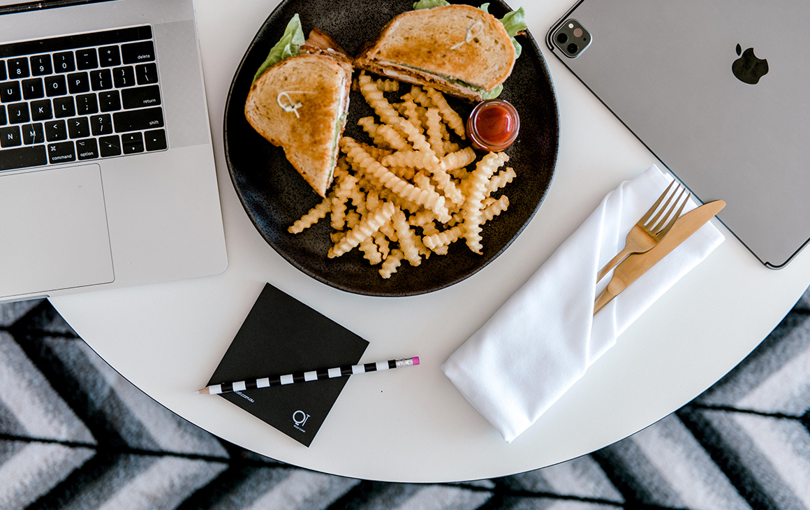 a club sandwich and fries on a plate on a table, in between two laptops
