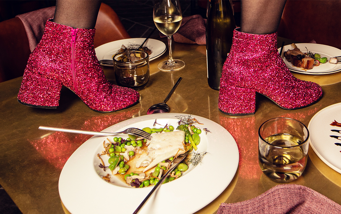 a pair of pink sparkly boots walks along a table laden with plates of food.