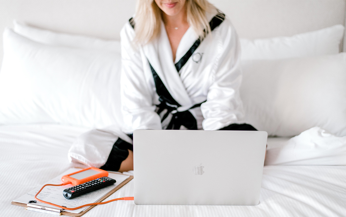 a woman, dressed in a white robe, sits on a plush, white bed while working on a laptop in front of her.