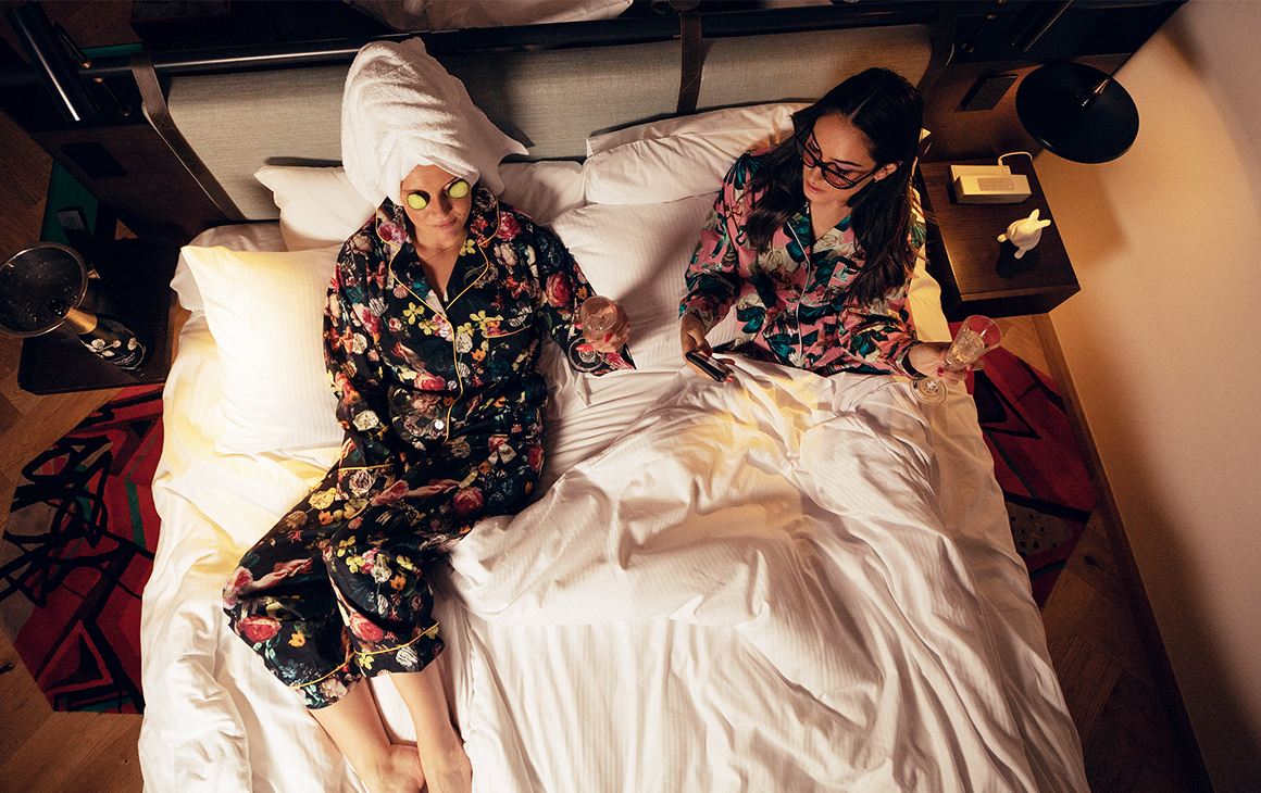 two women, in matching patterned PJ sets, recline on a double bed.