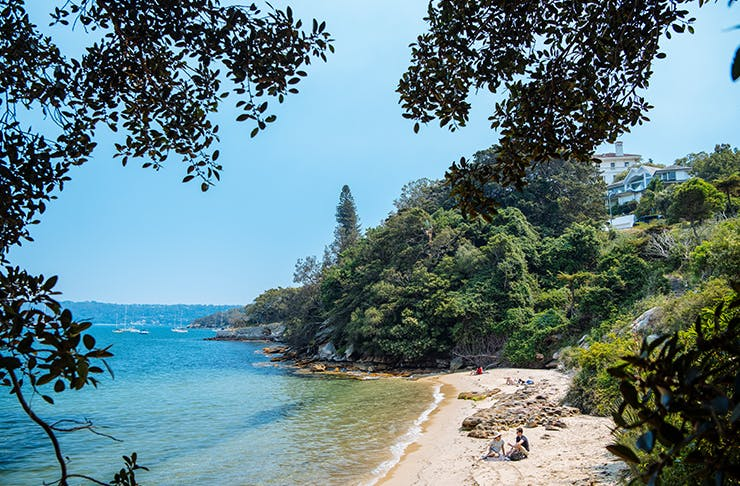 two people sitting on secluded beach in sydney harbour