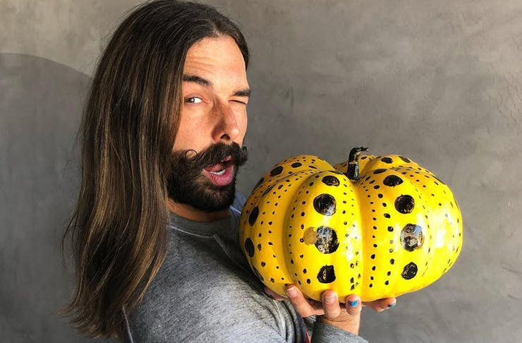 Jonathan Van Ness winks at the camera over his shoulder, while holding a yellow pumpkin.
