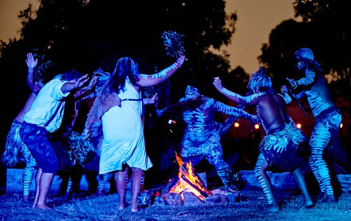 a group of First Nations people dance around a fire at night.