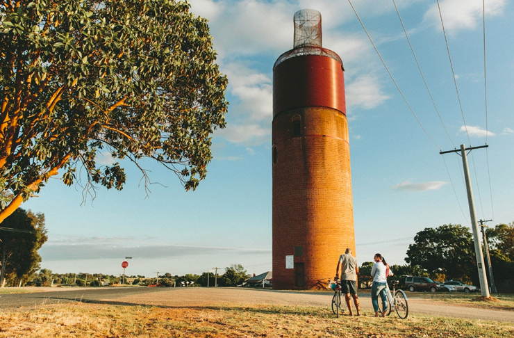 two people standing in front of rural tower on bike track