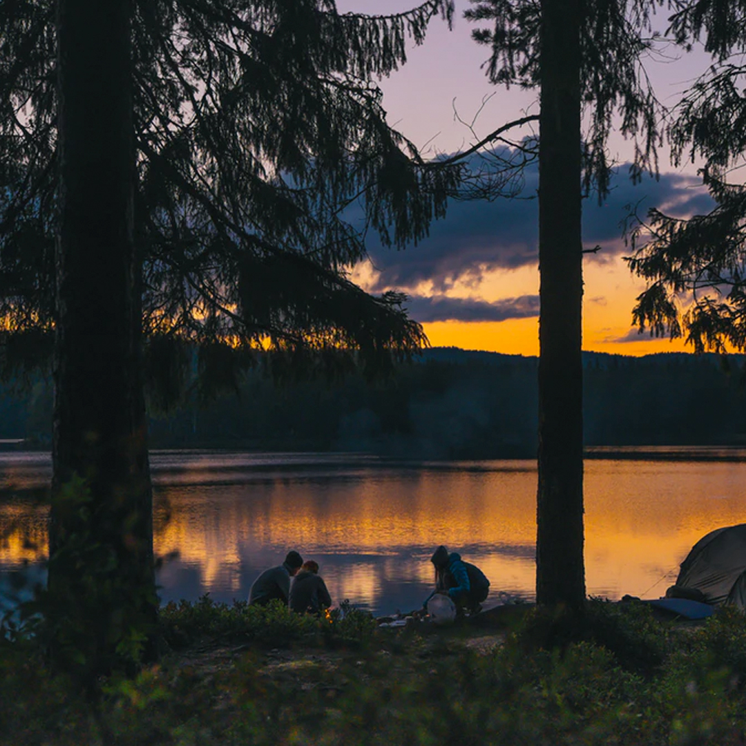 three people camping riverside at sunset